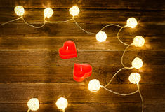 Two red candles in the shape of a heart and glowing lanterns made of rattan on a wooden background. Top view, space for text Stock Image