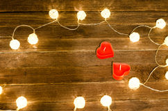 Two red candles in the shape of a heart and glowing lanterns made of rattan on a wooden background. Top view Stock Photos