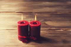Two red candles tied with red ribbon, the symbol of Valentine`s day, mimics the relationship of men and women Stock Photos