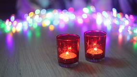 Two red candlestick and multi-colored lights in the background.  stock video