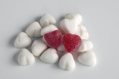 Two red candy hearts. Two red heart-shaped candies on pile of white candies to symbolize love or good matchmaking Stock Photography