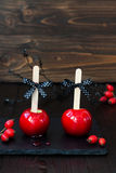 Two red caramel apples. Traditional dessert recipe for Halloween party. Selective focus. Copy space background Stock Photo