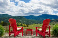 Two red chairs overlooking vineyard. Two empty red chairs are overlooking vineyards in the summer in the Okanagan Valley in British Columbia Royalty Free Stock Images