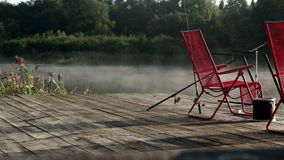 Two red chairs standing on fishing pier on background morning fog over water stock video footage