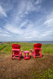 Two Red Chairs and Table looking out To the Sea Royalty Free Stock Images