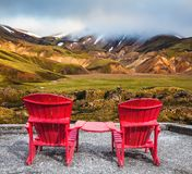 Two red chaise lounges connected by table. Travel to Iceland in the July. Two red chaise lounges connected by small table stand for tourists. Multi-colored royalty free stock photography
