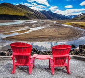 Two red chaise lounges for tourists. Multi-colored mountains from mineral rhyolite are lit with sun. Two red chaise lounges stand for tourists royalty free stock images
