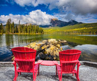 Two red chaise lounges for the tourists. Pyramid Mountain reflected in Pyramid Lake. Two red chaise lounges for the tourists connected among themselves by table stock images