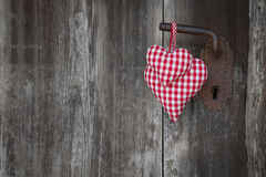 Two red checkered heart shape hanging on rusty door handle for v Stock Photos