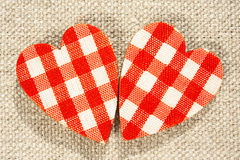 Two red checkered love hearts on burlap background. Royalty Free Stock Images