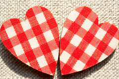 Two red checkered love hearts on burlap background. Stock Photo