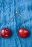 Two Red Cherries. Image of a two red cherries on blue cloth Royalty Free Stock Photography