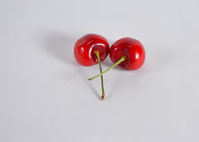 Two red cherries intertwine Stock Images