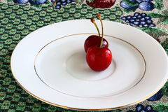 Two Red cherries on a plate Royalty Free Stock Photos
