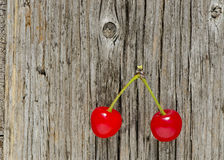 Two red cherry berry on wooden background Stock Photography