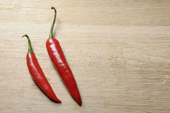 Two red chilies seen from top. Of the board Royalty Free Stock Image