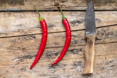 Two Red Chilli Pepper with Knife on wood background Stock Photography