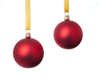 Two red Christmas balls. Hanging in yellow ribbons. Isolated on white Royalty Free Stock Photo