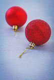 Two red christmas balls on gray background Stock Photography