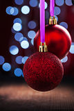 Two red christmas balls hanging on pink tape on old wooden table Stock Photography