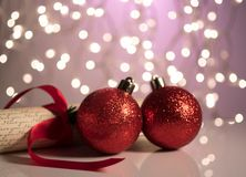 Two red Christmas balls on a reflective surface. Two red Christmas balls on a reflective surface on a bokeh background. Winter holidays concept royalty free stock image