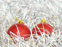 Two red Christmas balls and shiny tinsel of silver color, concept of holidays, Christmas and New Year. Close up stock photography