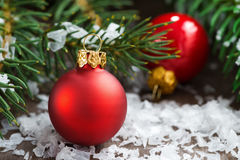 Two red Christmas balls in the snow and spruce branches Royalty Free Stock Images
