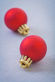 Two red christmas baubles on gray background Royalty Free Stock Photos