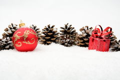 Two red christmas baubles with pine cones on snow in line on whi Stock Images