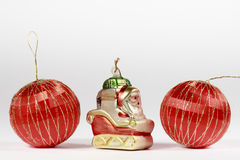 Two red Christmas baubles beside a Santa Claus figurine Royalty Free Stock Photography