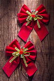 Two red christmas bows with gold ribbon and little bells on old Stock Photography