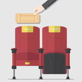 Two red cinema chair in flat design with hand holding blank movie ticket. Stock Images