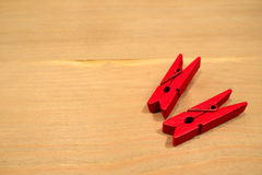 The two red clothespin placed on a wooden table. The two red clothespin placed on a wooden table in kitchen room Royalty Free Stock Photo