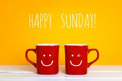 Two red coffee mugs with a smiling faces on a yellow background. With the phrase Happy sunday. Happy coffee mugs Royalty Free Stock Image