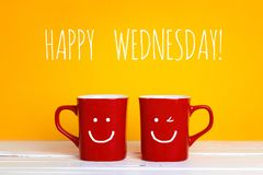 Two red coffee mugs with a smiling faces on a yellow background. With the phrase Happy wednesday. Happy coffee mugs stock images