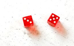 Two red craps dices showing Easy Eight number 3 and 5 overhead shot on white board royalty free stock images