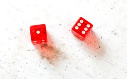 Two red craps dices showing Natural or Seven Out number 1 and 6 overhead shot on white board royalty free stock images