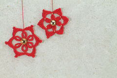 Two red crochet christmas stars with golden button. On sponged white background Stock Photos