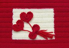 Two red crochet wool hearts and ribbon on crochet background. The concept for 14 February, romantic Valentine day, love affair,. Love story. Festive overhead royalty free stock image