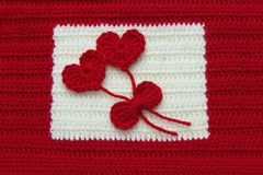 Two red crochet wool hearts and ribbon on crochet background. The concept for 14 February, romantic Valentine day, love affair,. Two red crochet wool hearts and stock photography