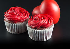 Two red cup cakes on and big red heart shape isolated on black b. Ackground - Romantic background  with text space - Conceptual love image Royalty Free Stock Photography