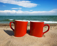 Two red cups. On a sunny beach Stock Photo