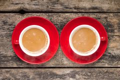Two Red Cups of Coffee with Milk on old Wood Background. Stock Photography