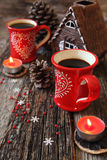 Two red cups of coffee,  pine cones and burning candle Stock Photo