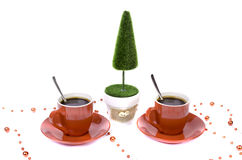 Two red cups of coffee tree and a basket of chocolate. Royalty Free Stock Photos