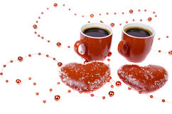 Two red cups of coffee and two hearts on a white background. Stock Photography