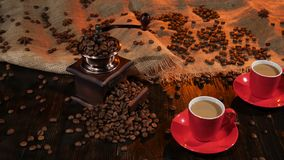 Two red cups with latte coffee on the wooden table. Table laid out burlap and coffee beans and anise, cup on saucer, coffee mill full of with coffee beans stock video footage