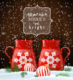 Two red cups with white snowflake, winter theme. Two red cups with white decorative snowflake on dark wooden background, with two balls and green needle branches Stock Images
