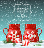 Two red cups with white snowflake, winter theme. Two red cups with white decorative snowflake in winter landscape, with two balls and green needle branches Stock Photography