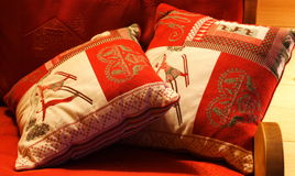 Two red cushions on a sofa Royalty Free Stock Images
